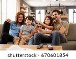 family sitting on sofa in open... | Shutterstock . vector #670601854