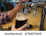 Small photo of Cropped hands of barmaid pouring drink from tap in glass at bar counter