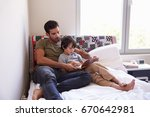father and son siting on bed... | Shutterstock . vector #670642981