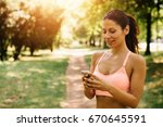 sporty woman using smart phone... | Shutterstock . vector #670645591