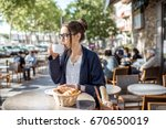 young woman having a breakfast... | Shutterstock . vector #670650019