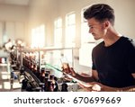 Small photo of Young man examining the quality of beer at brewery. Male inspector working at alcohol manufacturing factory checking the craft beer.