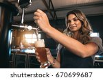 young woman dispensing beer in... | Shutterstock . vector #670699687