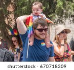 Small photo of June 30, 2017. Gan HaEm is a public garden in Haifa-Israel. Pride parade and a holiday of love, organized by LGBT community with the participation of city authorities. Dad with a baby on his shoulders
