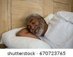 senior man sleeping on bed in... | Shutterstock . vector #670723765