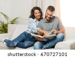 young smiling couple looking at ... | Shutterstock . vector #670727101