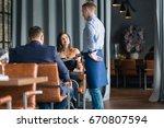 waiter taking an order for a... | Shutterstock . vector #670807594