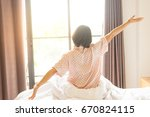 happy woman stretching in bed... | Shutterstock . vector #670824115