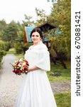 Small photo of Beautiful young bide in white wedding dress with wedding bouquet outdoor in a park