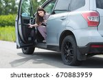 Small photo of Woman with car broken down, flat tire, close up