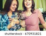 young happy women drinking wine ... | Shutterstock . vector #670931821