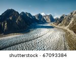 A Glacier Flows Away From Moun...