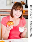 young woman enjoying a cup of coffee and sweet bun with fruits - stock photo