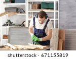 carpenter planing timber in... | Shutterstock . vector #671155819