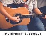 woman's hands playing acoustic... | Shutterstock . vector #671185135