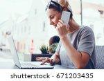 pretty woman yusing laptop in a ... | Shutterstock . vector #671203435