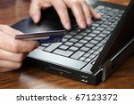 Man with credit card using a laptop computer for internet shopping - stock photo