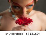 girl with butterfly make-up on face and flower - stock photo