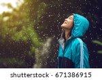Asian Woman Wearing A Raincoat...