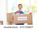 Small photo of Young volunteer with box of donations indoors