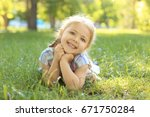 cute little girl lying on green ... | Shutterstock . vector #671750284