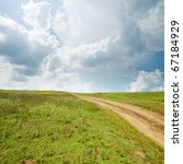 rural road in grass under cloudy sky - stock photo