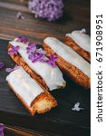Small photo of Beautiful eclair cakes with cream on wooden board with lilac flowers