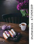 Small photo of Beautiful eclair cakes with cream and cup of tea on wooden board with lilac flowers