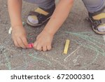 the child drawing a chalk on... | Shutterstock . vector #672000301