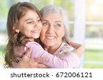 little girl hugging grandmother | Shutterstock . vector #672006121