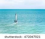 back view of a man wind surfing ... | Shutterstock . vector #672067021