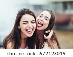 Two beautiful girlfriends having fun on the street
