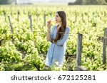 young woman tasting wine... | Shutterstock . vector #672125281