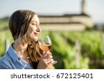 Young Woman Tasting Wine...