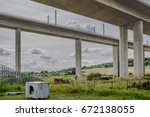 Small photo of ROCHESTER, KENT, UK - CIRCA JULY 2017: Illegally discarded washing machine seen abounded under a major motorway crossing, spanning the River Medway in Kent, showing its superstructure.
