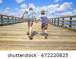children run on a wooden pier.... | Shutterstock . vector #672220825