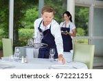 waiter setting glassware on...   Shutterstock . vector #672221251