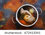 broth soup in a cooking pot on... | Shutterstock . vector #672413341