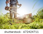 Gardening with a brushcutter - stock photo