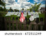 Small photo of Hundred dollar bills hang and dry on a rope against a blue cloudy sky. Money hangs among the drying clothes.