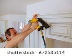 carpenter brad using nail gun... | Shutterstock . vector #672535114