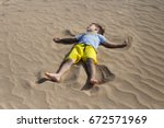 A Boy Is Lying On A Fine Sand...