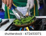 chef cooking vegetables on pan   Shutterstock . vector #672653371
