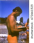 Small photo of USSR, ABKHAZIA, LESELIDZE VILLAGE - CIRCA 1983: Vintage photo of man on beach reading book in Leselidze, Abkhazia, USSR