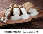 Small photo of scoop with white sand and lump sugar on brown wooden background and brown scoops