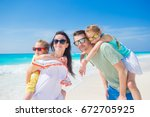 young family of four on beach... | Shutterstock . vector #672705925