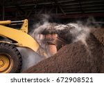 Small photo of A large compost pile being churned by a bulldozer.