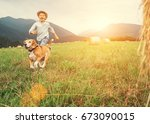 Boy And Dog Run Together On Th...