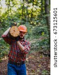 Small photo of The young, hard-working logger carries a log on his shoulder