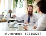 two professionals discussing... | Shutterstock . vector #673160287